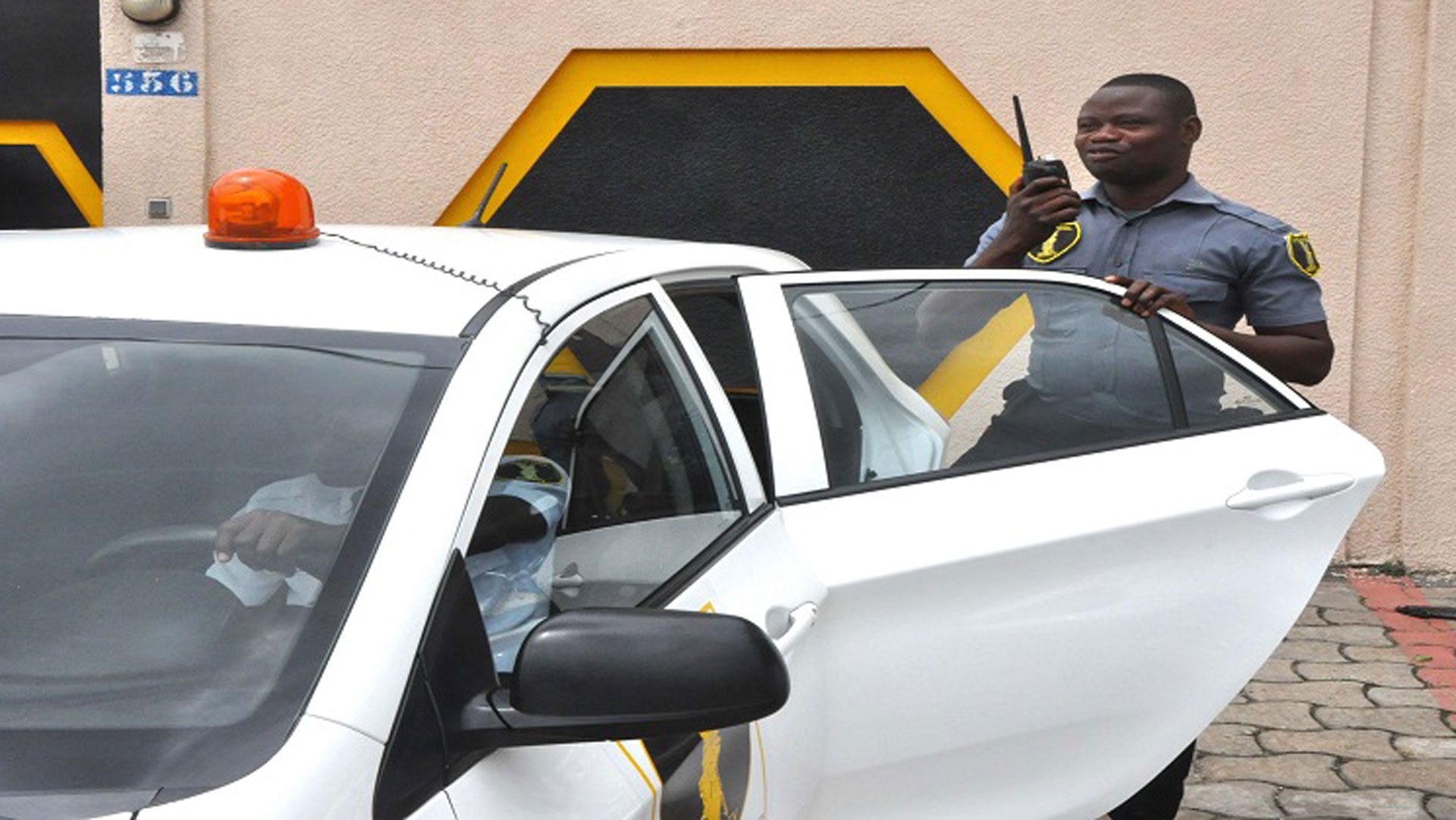 agent de gardiennage privée debout à coté d'une voiture